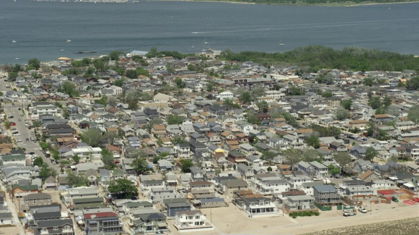 5K stock footage aerial video of a residential neighborhood near the water, Breezy Point, Queens, New York Aerial Stock Footage | AX83_225