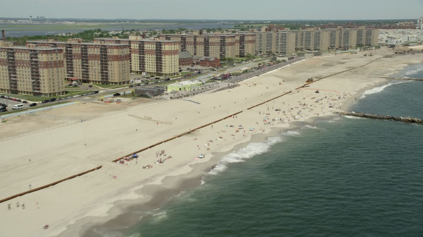 5K stock footage aerial video of beach goers and apartment complexes, Rockaway Beach, New York  Aerial Stock Footage AX83_229 | Axiom Images
