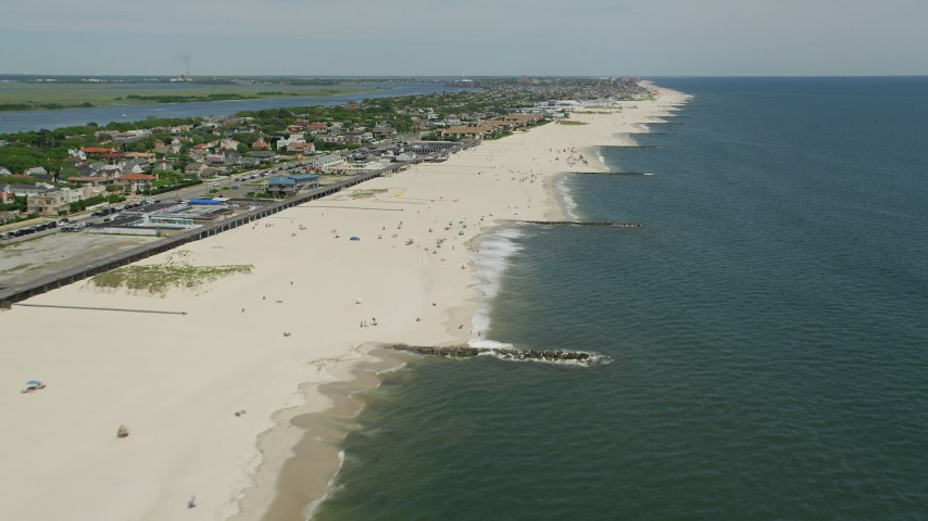 5K aerial video passing Atlantic Beach apartment complex and beach goers, Long Island, New York Aerial Stock Footage | AX83_235