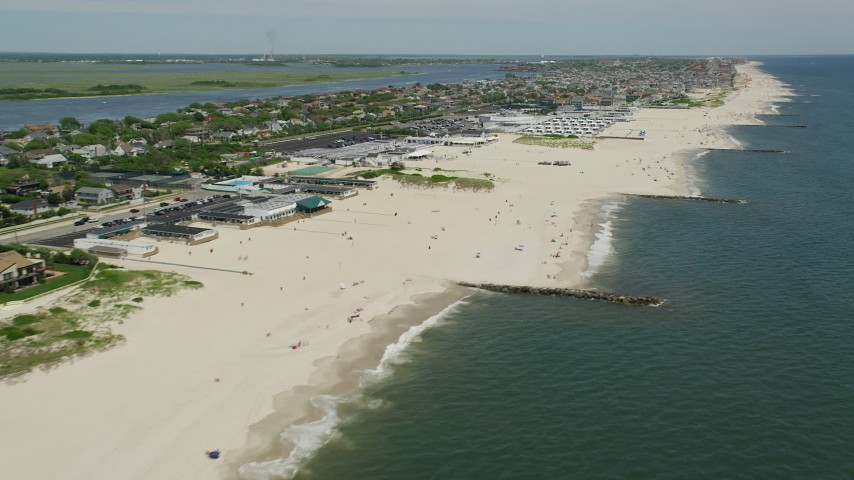 5K stock footage aerial video of beachgoers and beachfront neighborhoods near the Sands Atlantic Beach, New York Aerial Stock Footage | AX83_236
