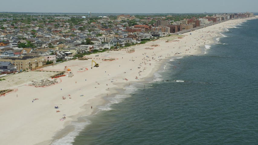 5K stock footage aerial video flying by beach-goers on a beach, Long Beach, New York Aerial Stock Footage | AX83_238