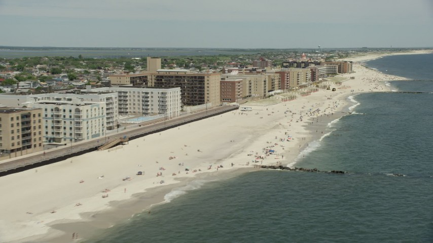 5K stock footage aerial video tilting to a Crowd of Sunbathers on the Beach, Long Beach, New York Aerial Stock Footage | AX83_242