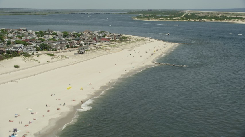 5K stock footage aerial video of a small group of people on the beach near beachfront homes, Point Lookout, New York Aerial Stock Footage | AX83_248
