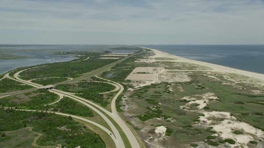 5K stock footage aerial video flying between coastal road and beach at Jones Beach State Park, Wantagh, New York Aerial Stock Footage | AX83_251