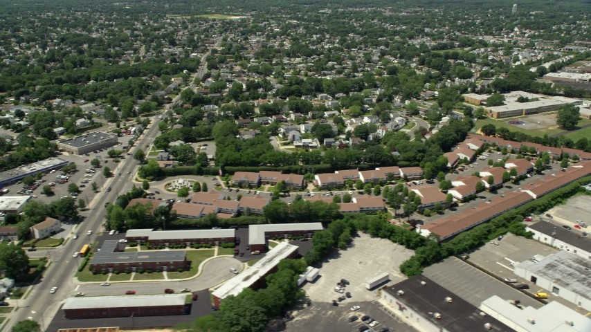 5K stock footage aerial video flying by suburban neighborhoods to reveal warehouses, Republic Airport in Farmingdale, New York Aerial Stock Footage   AX83_265E