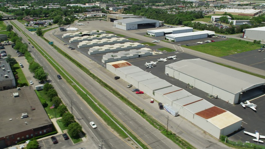 5K stock footage aerial video flying by warehouse buildings and airplane hangars at Republic Airport in Farmingdale, New York Aerial Stock Footage   AX83_267