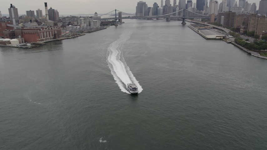 5k aerial video Flying over ferry, East River, Manhattan Bridge, Lower Manhattan skyline, New York Aerial Stock Footage | AX84_101