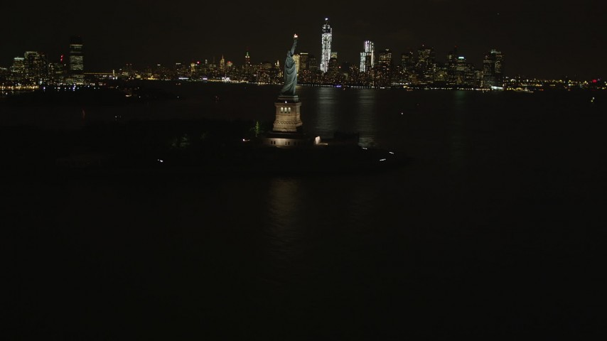 4K stock footage aerial video Revealing Statue of Liberty, Lower Manhattan skyline, New York, New York, night Aerial Stock Footage | AX85_003