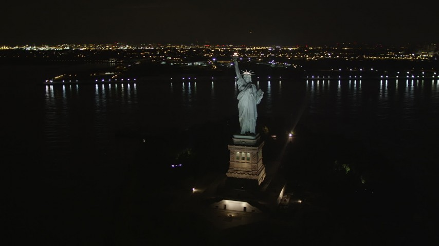 4K stock footage aerial video Orbiting the Statue of Liberty, New York, New York, night Aerial Stock Footage | AX85_005
