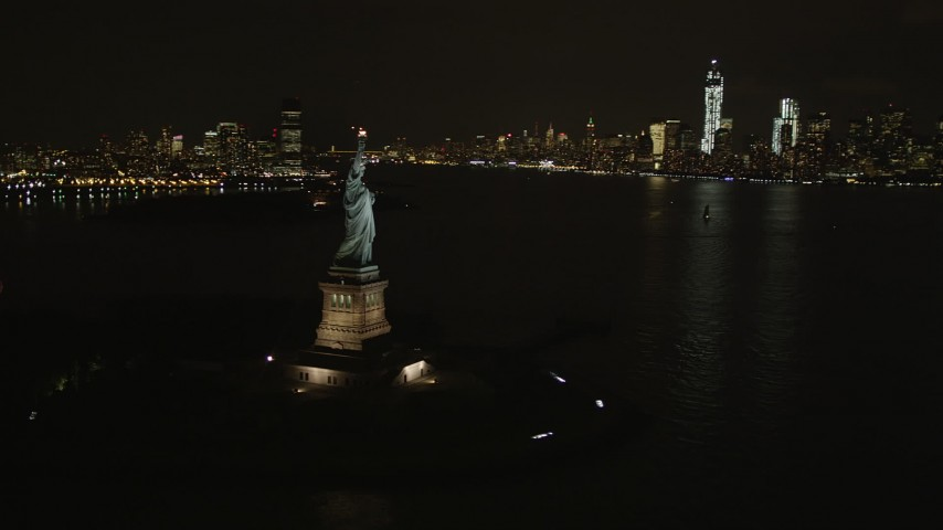 4K stock footage aerial video of Statue of Liberty, Lower Manhattan skyline, New York, New York, night Aerial Stock Footage | AX85_009