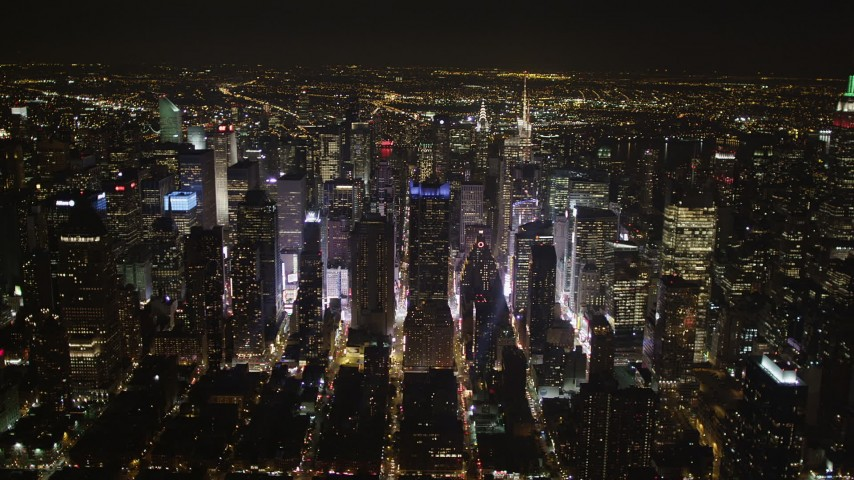 4K stock footage aerial video Skyscrapers in Midtown Manhattan, streets, New York, New York, night Aerial Stock Footage | AX85_093