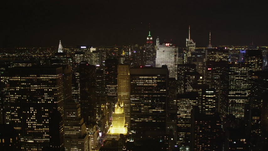 4K stock footage aerial video Flying by skyscrapers in Midtown Manhattan, New York, New York, night Aerial Stock Footage | AX85_106
