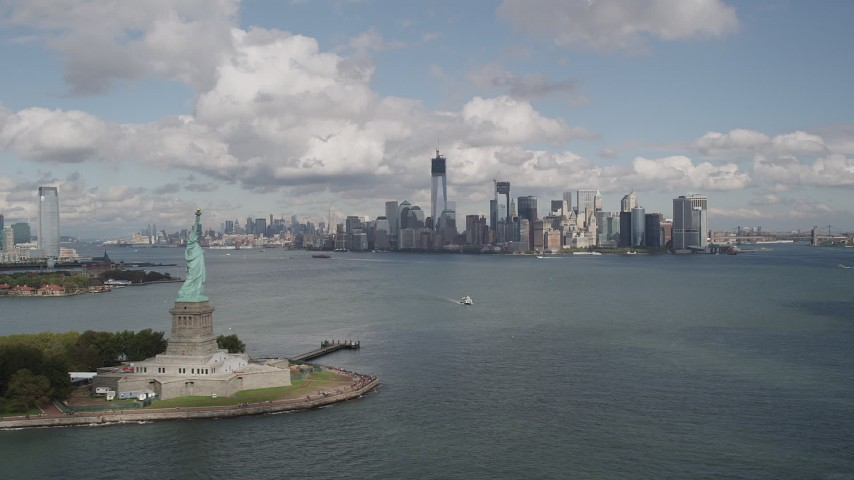 5k aerial video Statue of Liberty, Liberty Island, Lower Manhattan skyline, New York, New York Aerial Stock Footage | AX87_002