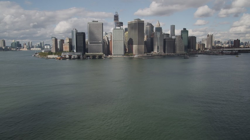 4K stock footage aerial video Tilt up from bay to reveal Lower Manhattan skyscrapers, New York, New York Aerial Stock Footage | AX87_046