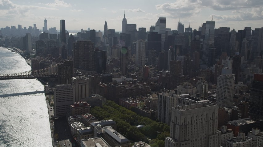4K aerial video Fly by Midtown Manhattan skyscrapers, from East River, New York, New York Aerial Stock Footage | AX87_188