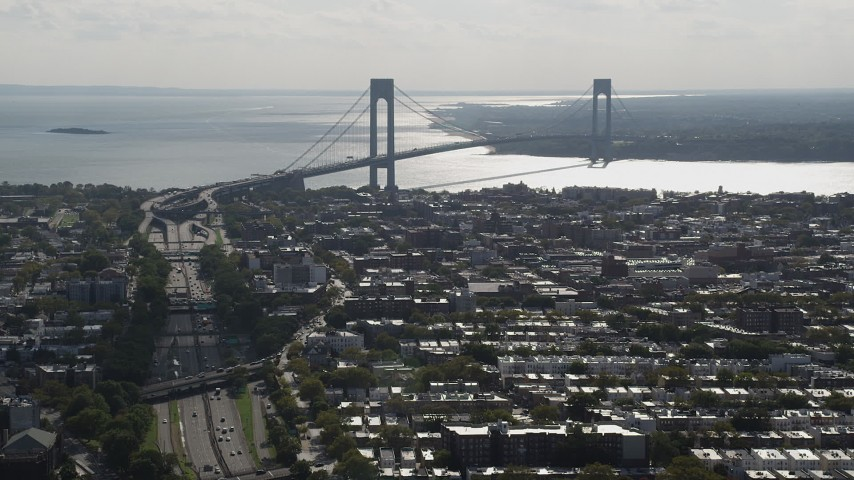 4K stock footage aerial video of the Verrazano-Narrows Bridge, seen from Brooklyn row houses, New York Aerial Stock Footage AX88_030 | Axiom Images