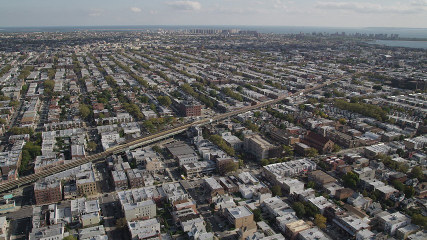4K stock footage aerial video of flying over row houses, tilt to railroad tracks, Brooklyn, New York Aerial Stock Footage | AX88_033
