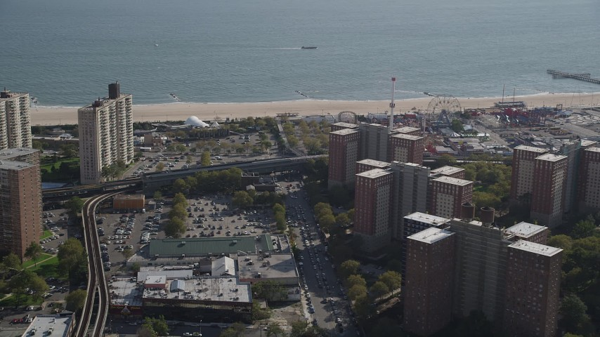 4K stock footage aerial video flyby apartment buildings toward the beach, Luna Park in Coney Island, Brooklyn, New York Aerial Stock Footage | AX88_042