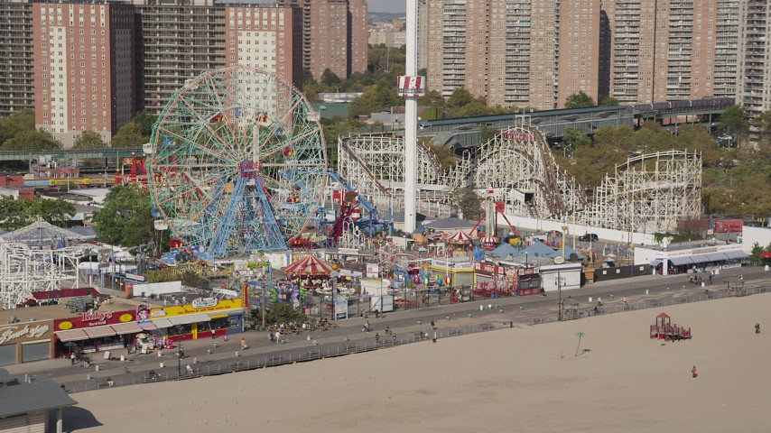 4K stock footage aerial video of flying away from a Ferris wheel and rollercoasters at Luna Park, Coney Island, Brooklyn, New York Aerial Stock Footage | AX88_049
