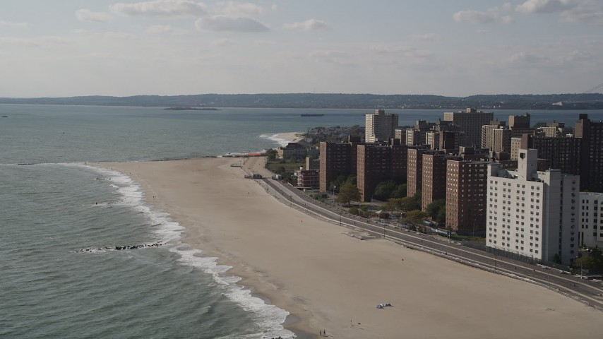 4K stock footage aerial video of flying by Coney Island Beach and apartment buildings in Brooklyn, New York, New York Aerial Stock Footage | AX88_051