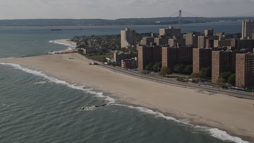 Flying by Coney Island Beach, Verrazano-Narrows Bridge, Brooklyn, New York Aerial Stock Footage | AX88_052