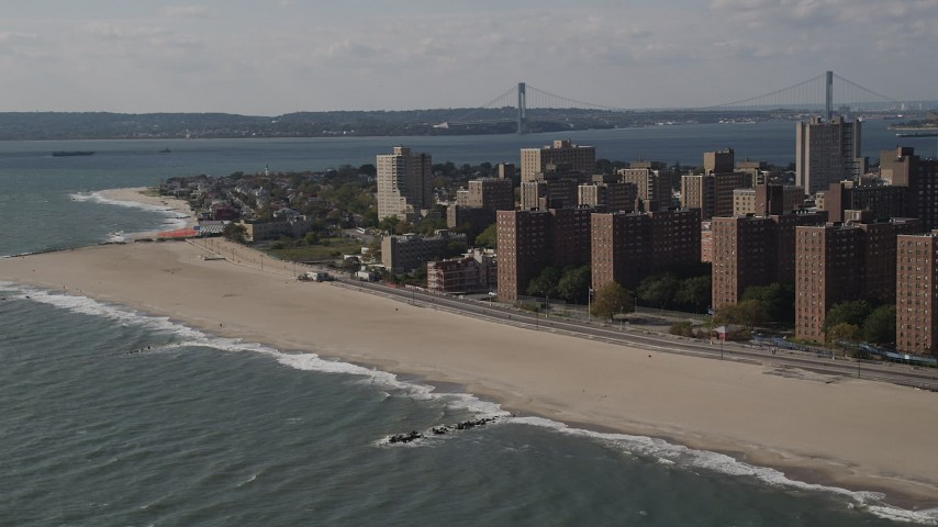 4K stock footage aerial video of flying by Coney Island Beach, with a view of the Verrazano-Narrows Bridge, Brooklyn, New York Aerial Stock Footage | AX88_052
