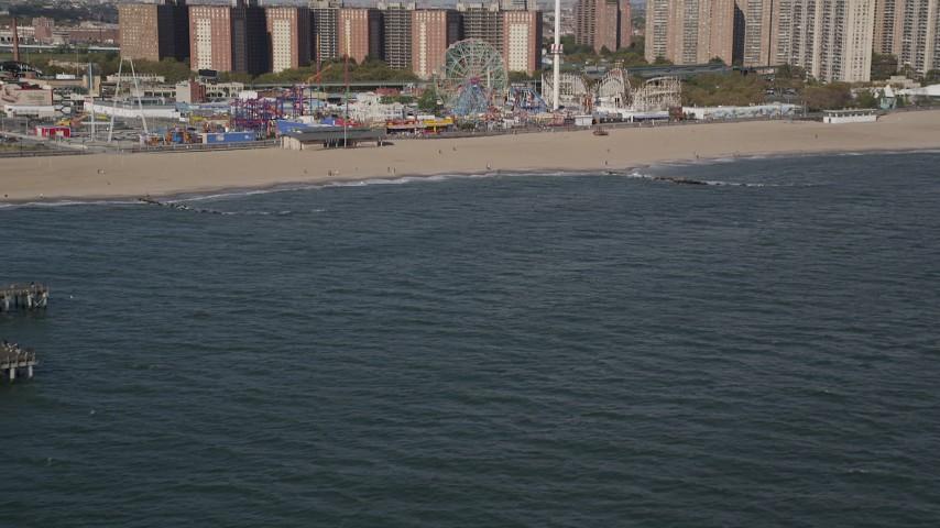 Tilt from Atlantic Ocean, reveal Luna Park, Coney Island, Brooklyn, New York Aerial Stock Footage   AX88_054