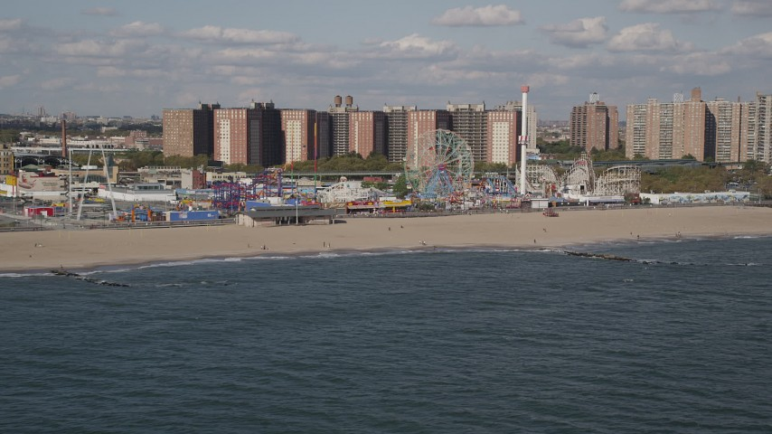 4K stock footage aerial video tilt from Atlantic Ocean, reveal Luna Park and Coney Island Beach, Brooklyn, New York Aerial Stock Footage | AX88_054