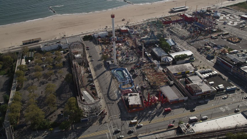 4K stock footage aerial video of flying by Luna Park's beachfront rides in Coney Island, Brooklyn, New York, New York Aerial Stock Footage | AX88_058