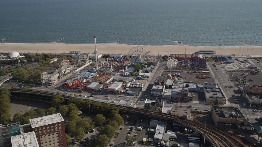 4K stock footage aerial video of flying away from rides and beach at Luna Park, Coney Island, Brooklyn, New York Aerial Stock Footage | AX88_059