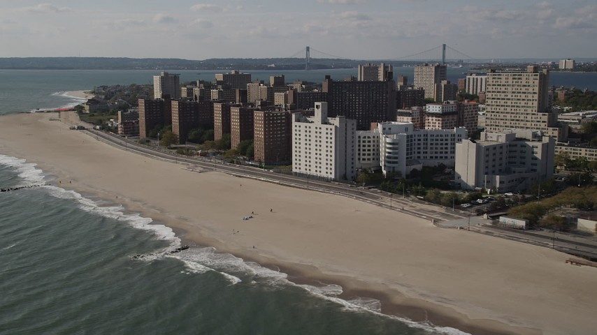 4K aerial video of passing by Coney Island Beach and apartment buildings, Brooklyn, New York Aerial Stock Footage | AX88_063