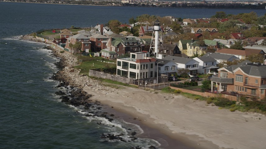 Flying by oceanfront homes, Coney Island, Brooklyn, New York, New York Aerial Stock Footage | AX88_071