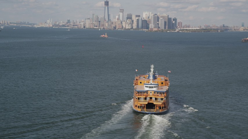 4K stock footage aerial video of a Staten Island Ferry sailing New York Harbor and Lower Manhattan skyline, New York Aerial Stock Footage | AX88_094