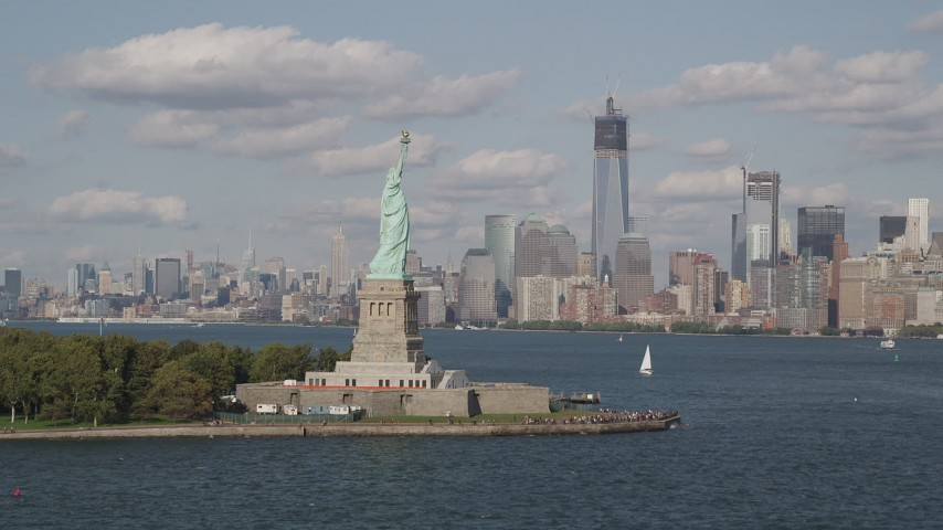 4K stock footage aerial video approach Statue of Liberty, with Lower Manhattan skyline in background, New York Aerial Stock Footage | AX88_096
