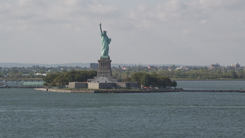 4K stock footage aerial video tilt from New York Harbor, revealing Statue of Liberty, New York, New York Aerial Stock Footage | AX88_102