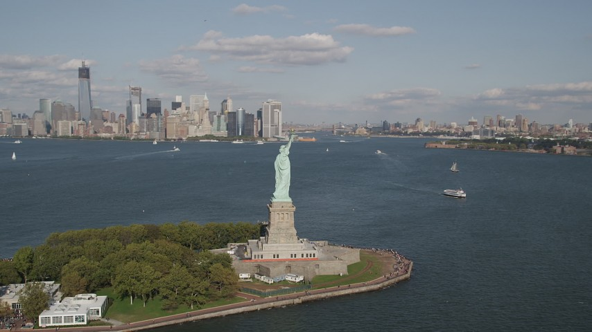 5K aerial video of flying by Statue of Liberty, with views of Lower Manhattan skyline and Brooklyn, New York Aerial Stock Footage | AX88_110