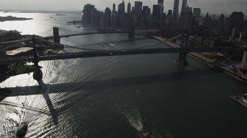 4K aerial video tilt from East River, reveal Brooklyn Bridge, Manhattan Bridge, and Lower Manhattan skyscrapers, New York Aerial Stock Footage | AX88_124