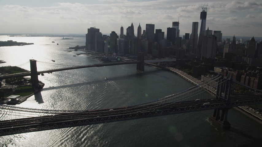 4K stock footage aerial video fly over Manhattan Bridge, approach Brooklyn Bridge and Lower Manhattan skyscrapers, New York Aerial Stock Footage | AX88_125