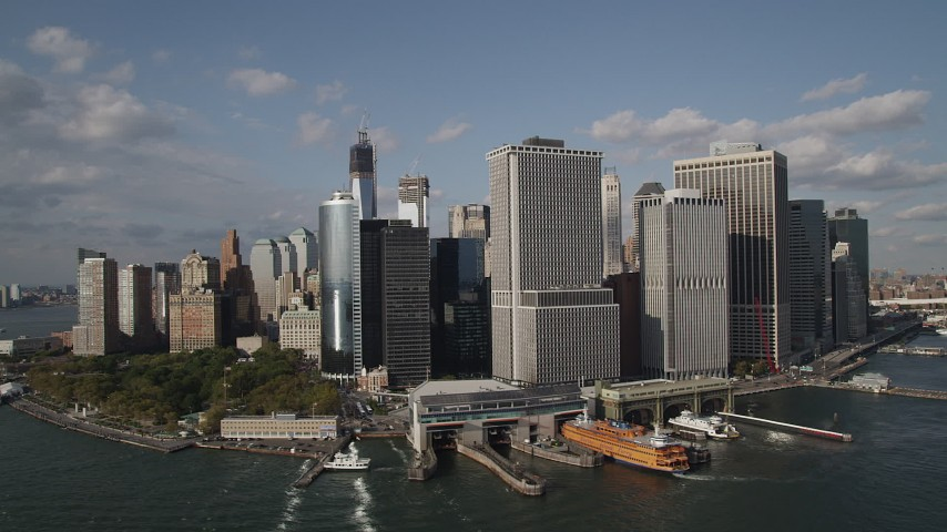 4K stock footage aerial video of passing by Battery Park, ferry terminal, and riverfront skyscrapers in Lower Manhattan, New York, New York Aerial Stock Footage | AX88_160