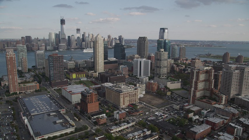 4K stock footage aerial video of city skyscrapers and Lower Manhattan skyline in background, Downtown Jersey City, New Jersey Aerial Stock Footage | AX88_171