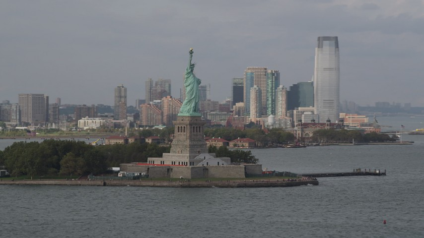 4K stock footage aerial video of the Statue of Liberty on Liberty Island, Jersey City in the background, New York Aerial Stock Footage | AX88_194