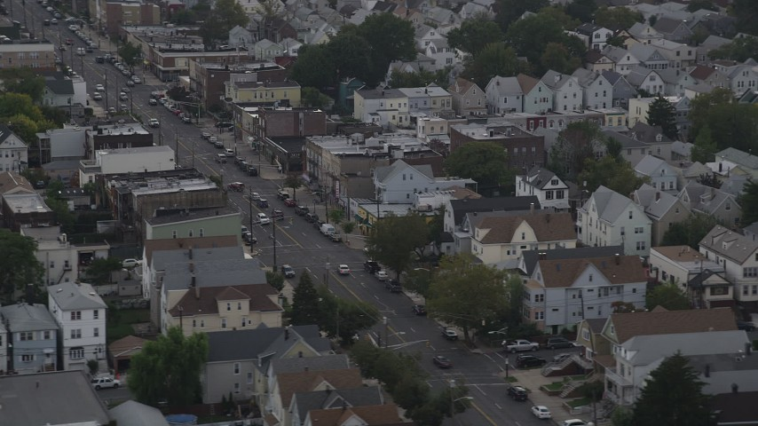 4K stock footage aerial video of flying by urban neighborhoods and a broad city street, Jersey City, New Jersey Aerial Stock Footage | AX88_199