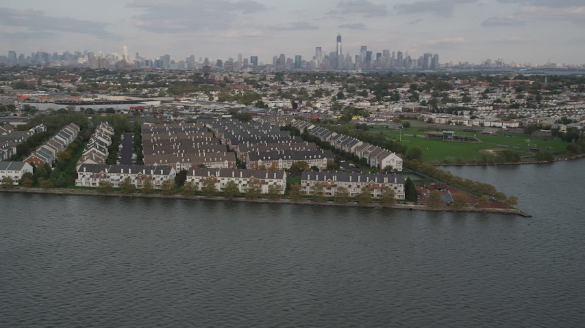 4K aerial video of flying by waterfront condominiums, Lower Manhattan skyline in background, Jersey City, New Jersey Aerial Stock Footage | AX88_202