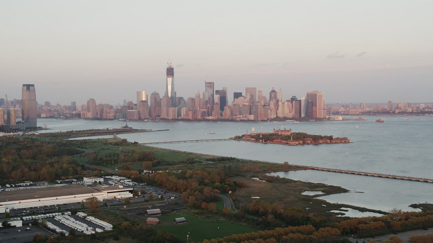 4K aerial video Approaching Ellis Island, Lower Manhattan skyline, New York, New York, sunset Aerial Stock Footage | AX89_001