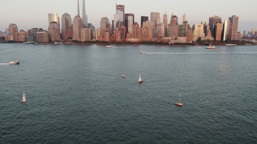 4K stock footage aerial video of Sailboats, New York Harbor, revealing Lower Manhattan, New York, sunset Aerial Stock Footage | AX89_002