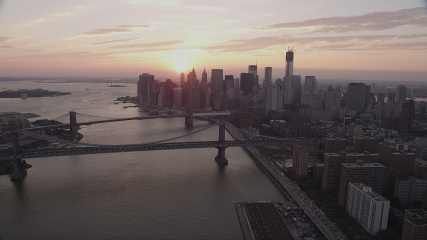 4K aerial video Fly over East River, reveal Lower Manhattan, Bridges, New York, sunset Aerial Stock Footage | AX89_012
