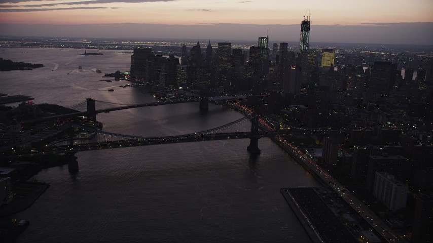 4K aerial video of the Brooklyn Bridge, Manhattan Bridge, East River, Lower Manhattan, New York, twilight Aerial Stock Footage | AX89_106