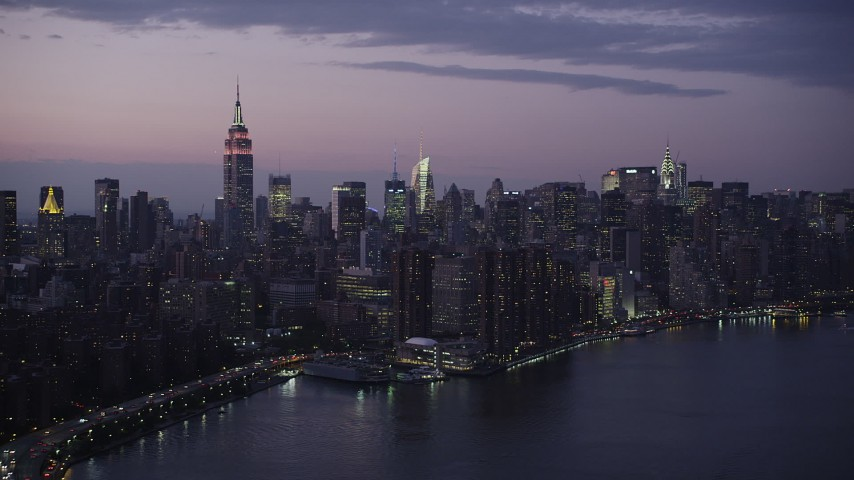 4K stock footage aerial video Flying by Midtown Manhattan, seen from East River, New York, New York, twilight Aerial Stock Footage | AX89_114