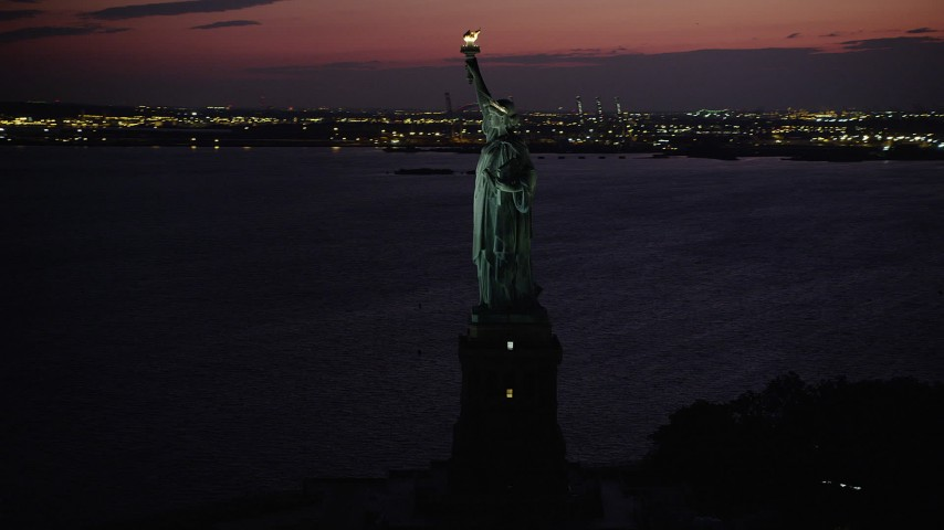 4K aerial video Flying by the Statue of Liberty, Liberty Island, New York, New York, twilight Aerial Stock Footage | AX89_138