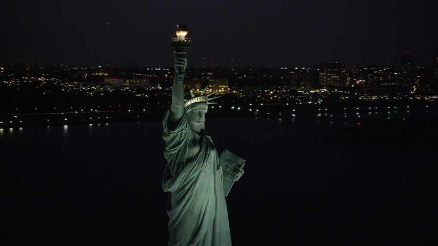 4K aerial video Flying by the Statue of Liberty, Liberty Island, New York, New York, night Aerial Stock Footage | AX89_142